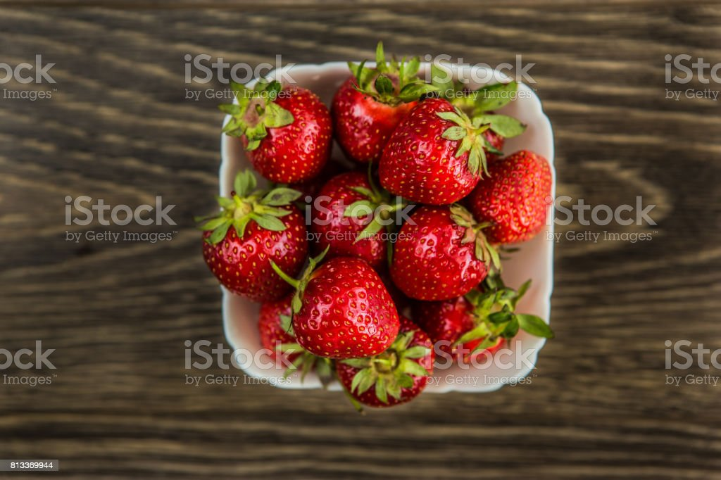 A small white porcelain bowl filled with juicy fresh ripe red strawberries. Textured table top. Fresh strawberries. Strawberries in a Bowl stock photo