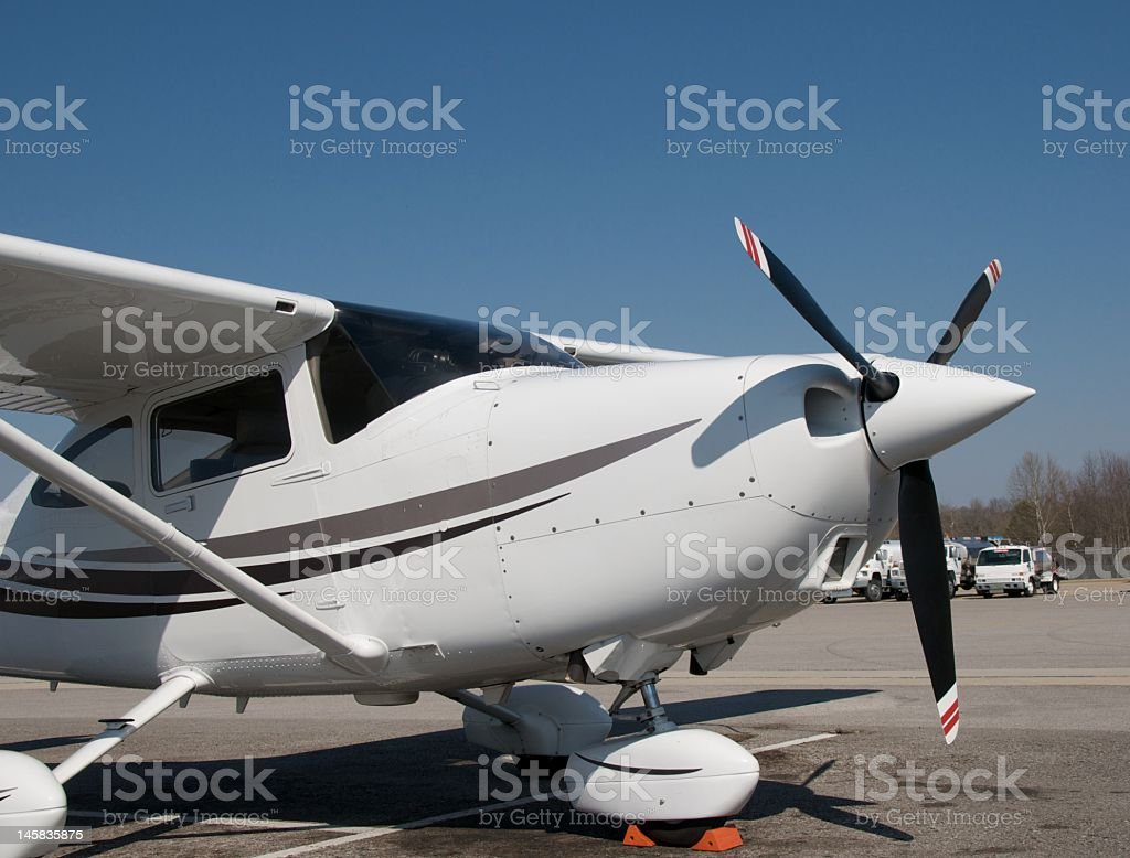 Small white single engine aircraft with a black propeller stock photo