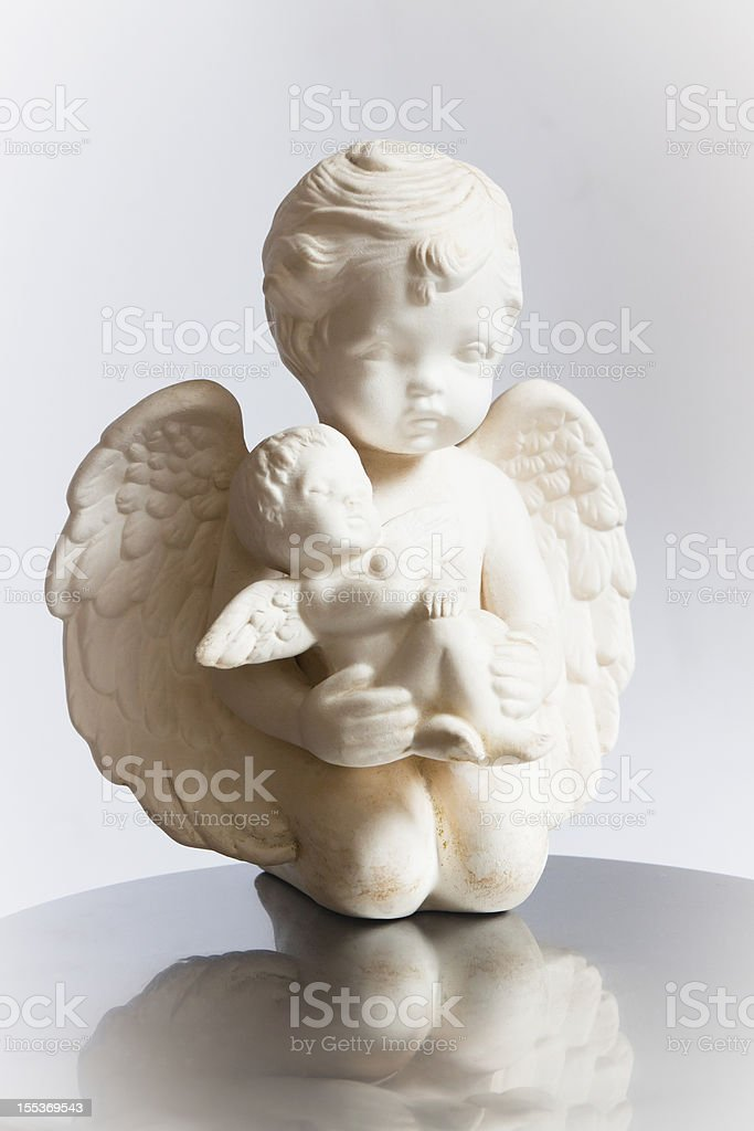 Small white statue of kneeling angel holding baby angel stock photo