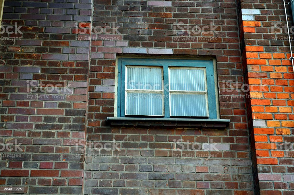 small window of an industrial building with brick wall stock photo