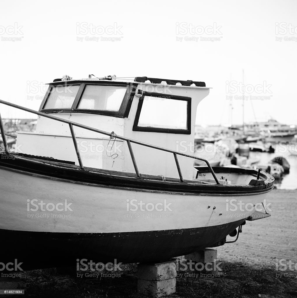 Small wooden boat moored on the sandy beach stock photo