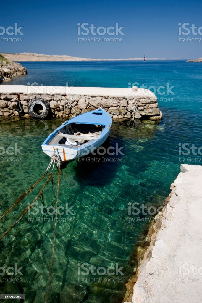 Small wooden boat on the crystal sea water royalty-free stock photo
