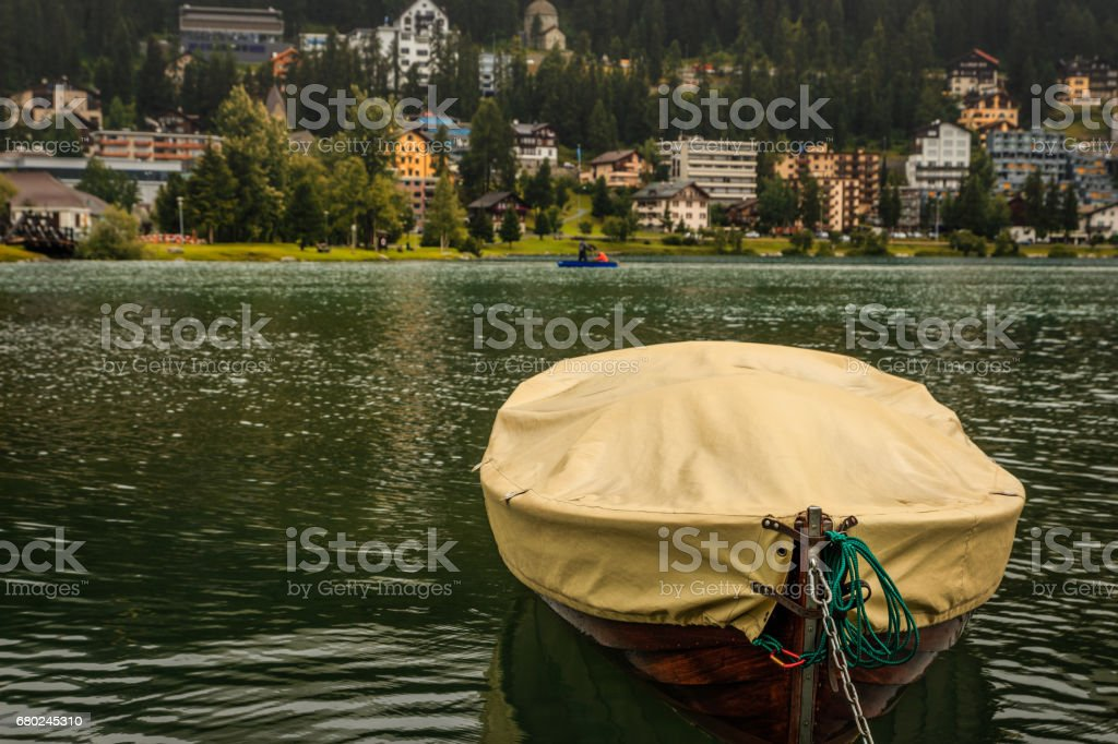 Small wooden boat under yellow tarpaulin on mountain lake, St. Moritz, Grisons, Switzerland stock photo