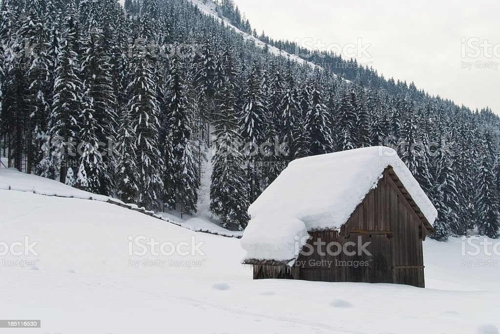 Small wooden cottage in winter wonderland stock photo
