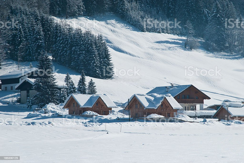 Small wooden cottages in winter wonderland stock photo