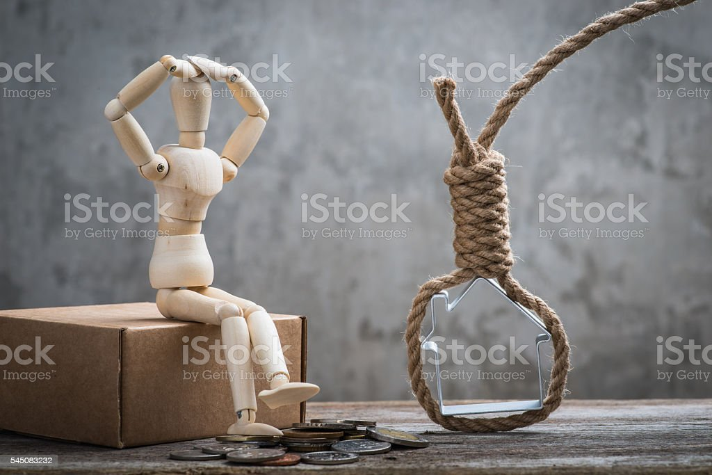 Small wooden dummy sitting with hangman's noose, house and coins stock photo