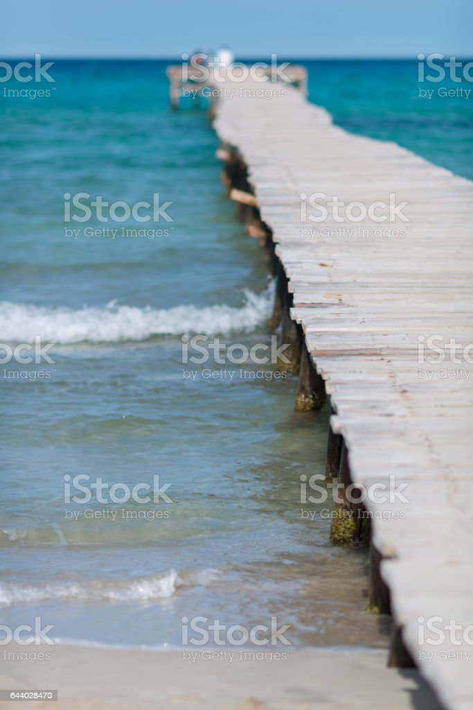 small wooden foodbridge or runway to the ocean - jetty stock photo