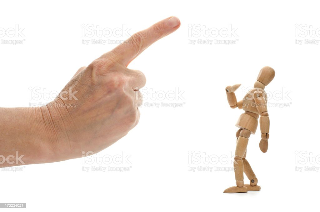Small wooden mannequin and human hand with pointed finger stock photo