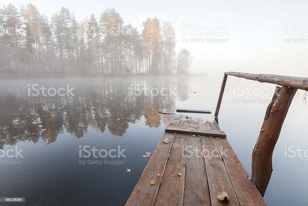 Small wooden pier on still lake in cold foggy morning royalty-free stock photo
