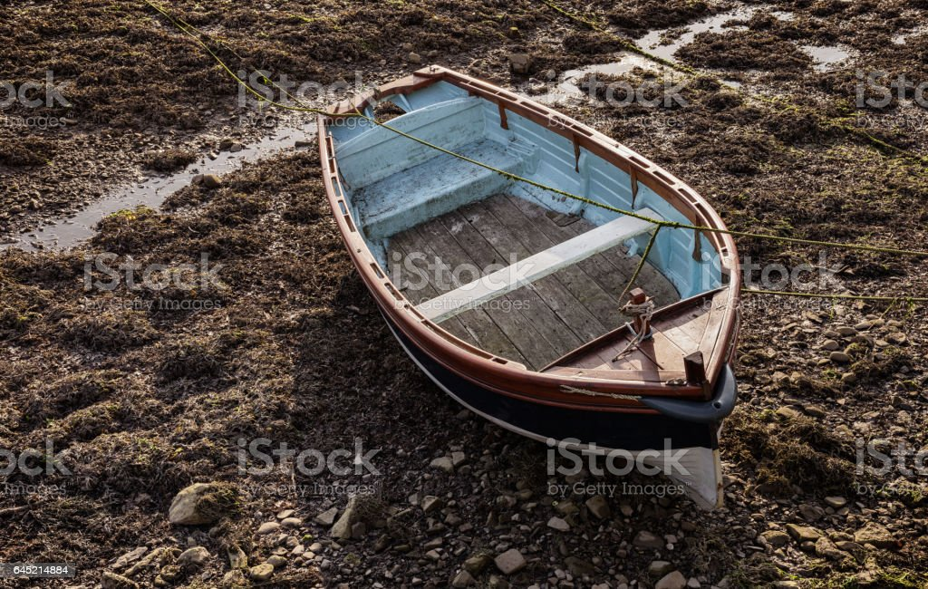 Small wooden rowboat moored at low tide stock photo