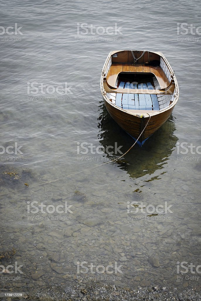 Small wooden rowing boat moored on a shingle beach royalty-free stock photo