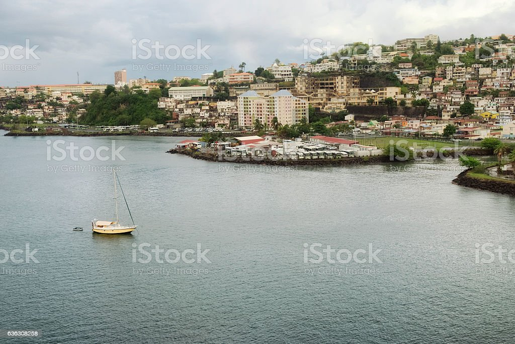 Small yellow boat and many colorful buildings on the coast stock photo