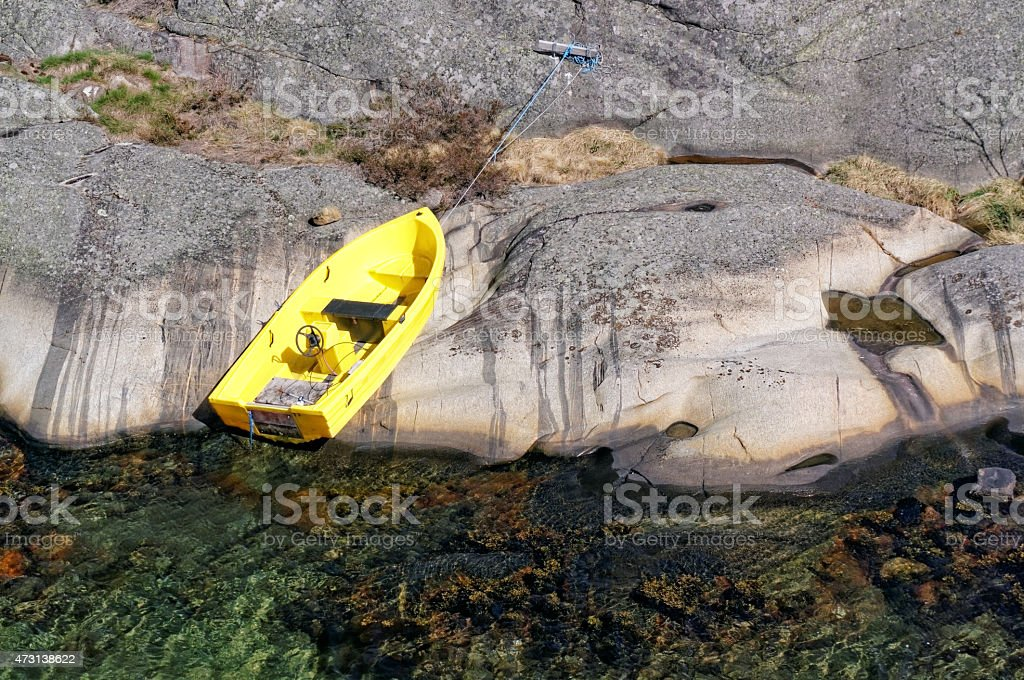 Small yellow boat moored to a rock stock photo