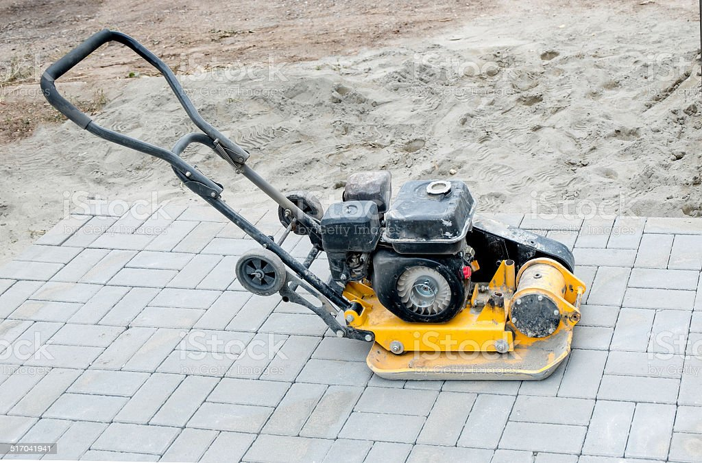 Small yellow compactor standing on new gray  pavement stock photo