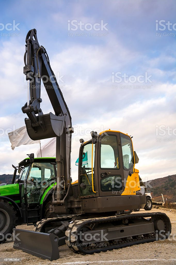 Small yellow excavator and green tractor. stock photo