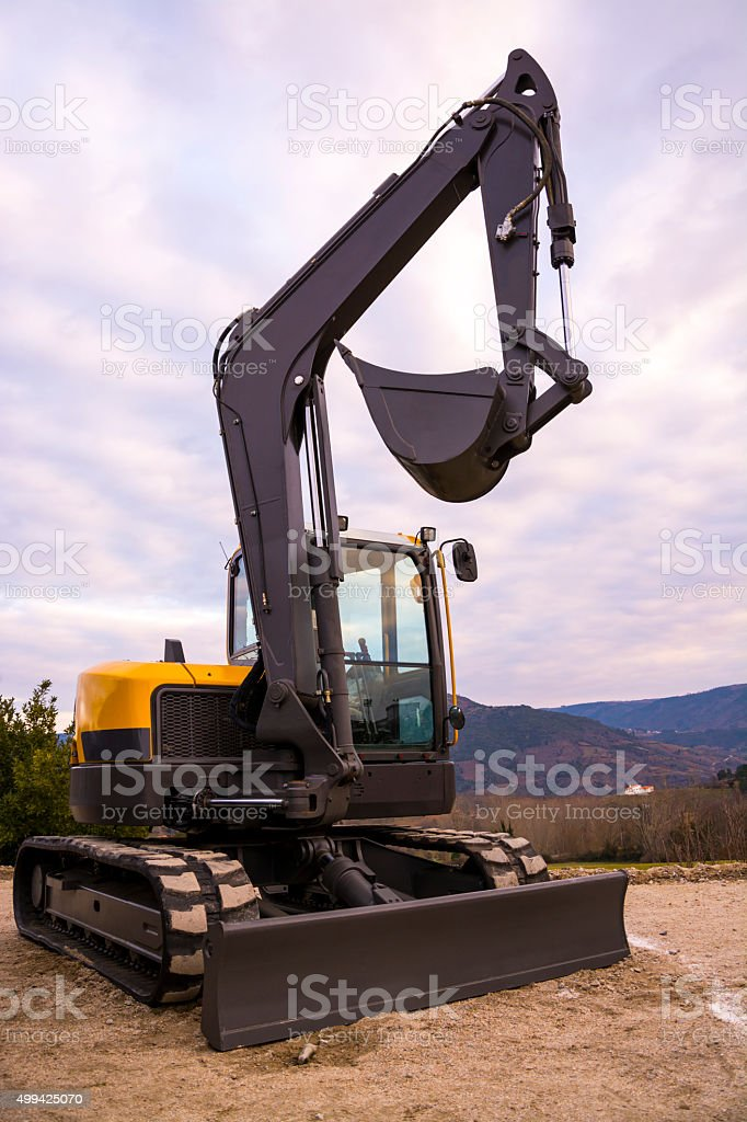 Small yellow excavator parked on a cloudy day. stock photo