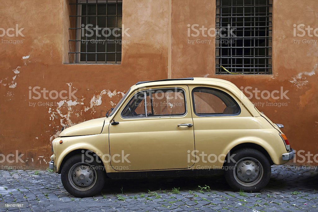 Small yellow vintage car in Rome royalty-free stock photo