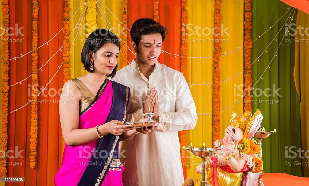 smart and young indian couple and ganpati pujan or puja stock photo
