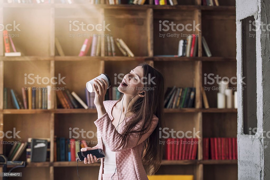 Smart beautiful young woman in headphones with a glass stock photo