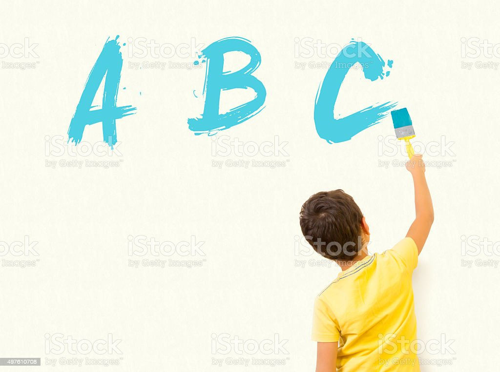 Smart boy writing alphabet letters ABC on the wall stock photo