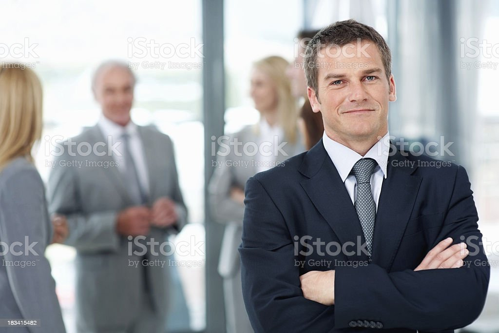 Smart business man with colleagues in background royalty-free stock photo