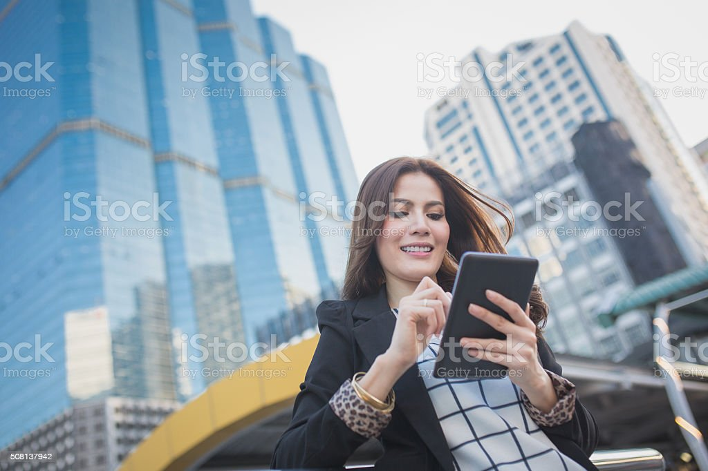 Smart business woman looking confident and smiling holding tablet computer stock photo