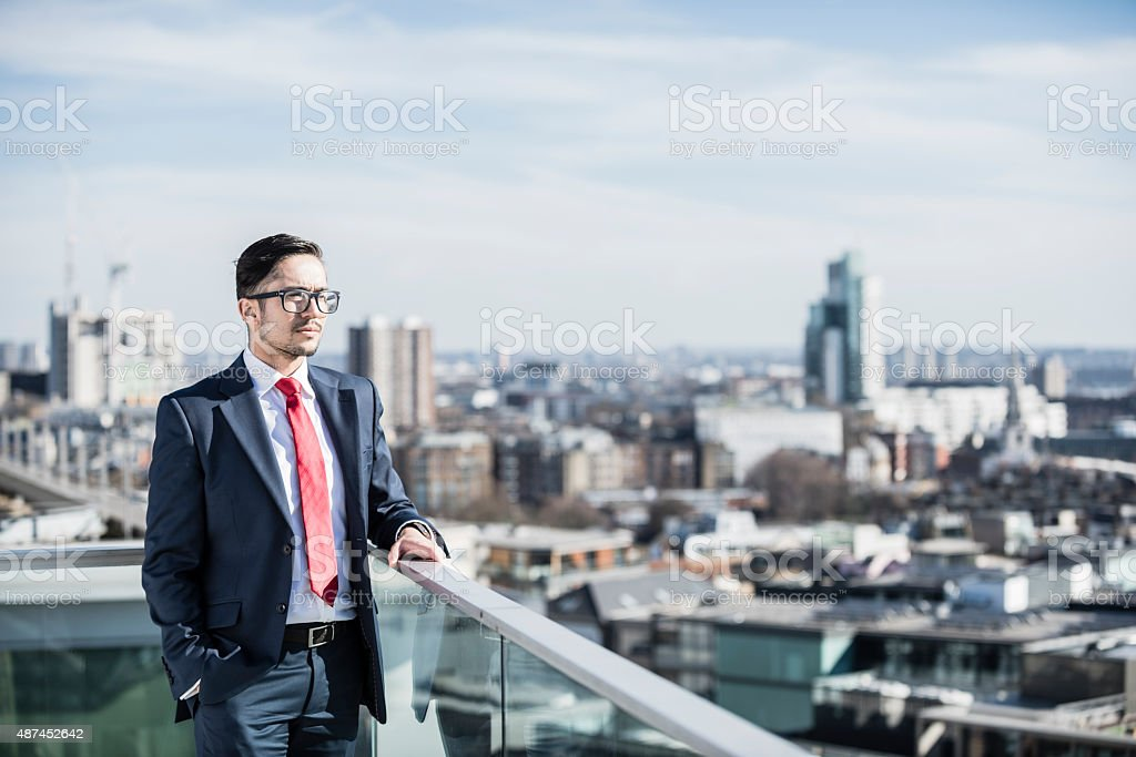 Smart businessman looking out over city stock photo