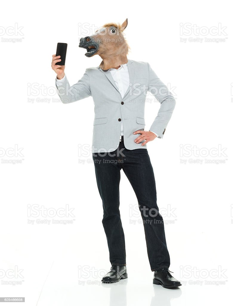 Smart casual man in horse costume taking a selfie stock photo