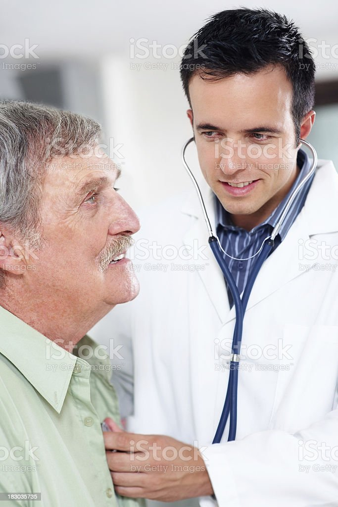 Smart doctor listening to a senior patient's heartbeat royalty-free stock photo