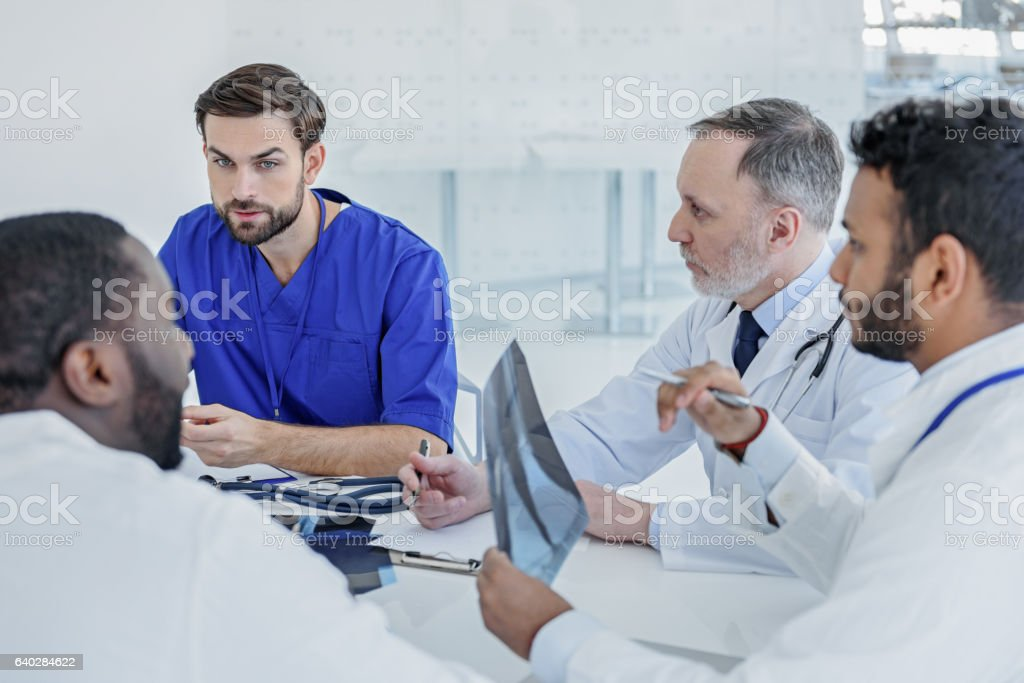 Smart doctors gathering council at clinic stock photo