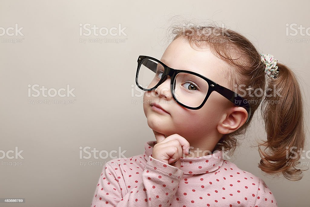 Smart dreaming kid girl in glasses looking stock photo