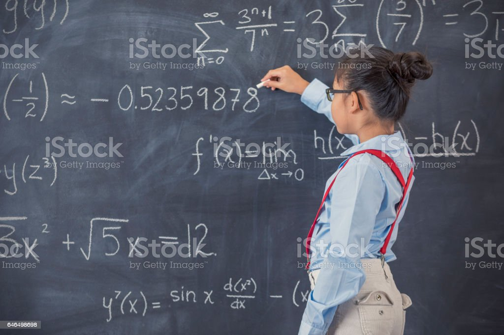 Smart elementary age girl works on math problem stock photo