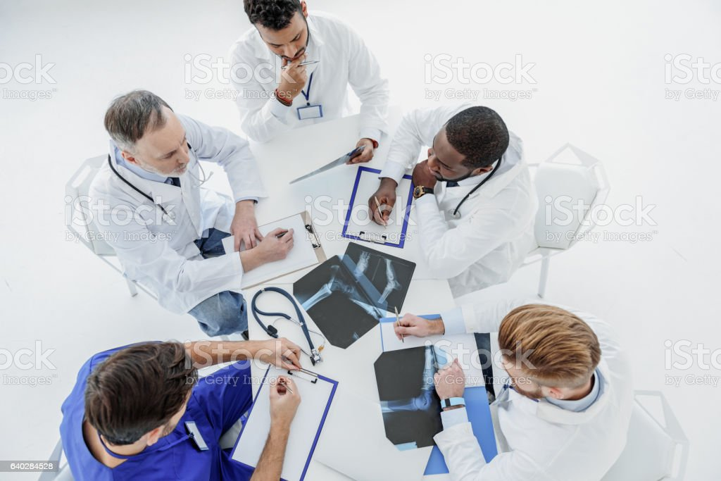 Smart general practitioners having conversation at desk stock photo