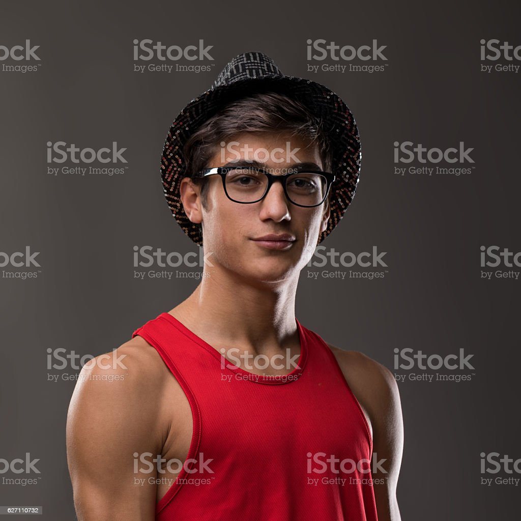 smart guy smiling with hat and red tank top stock photo