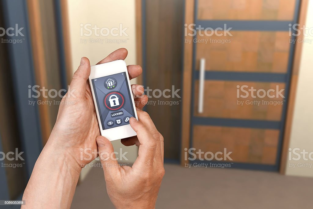 Smart home automation: locking house door with security remote control stock photo