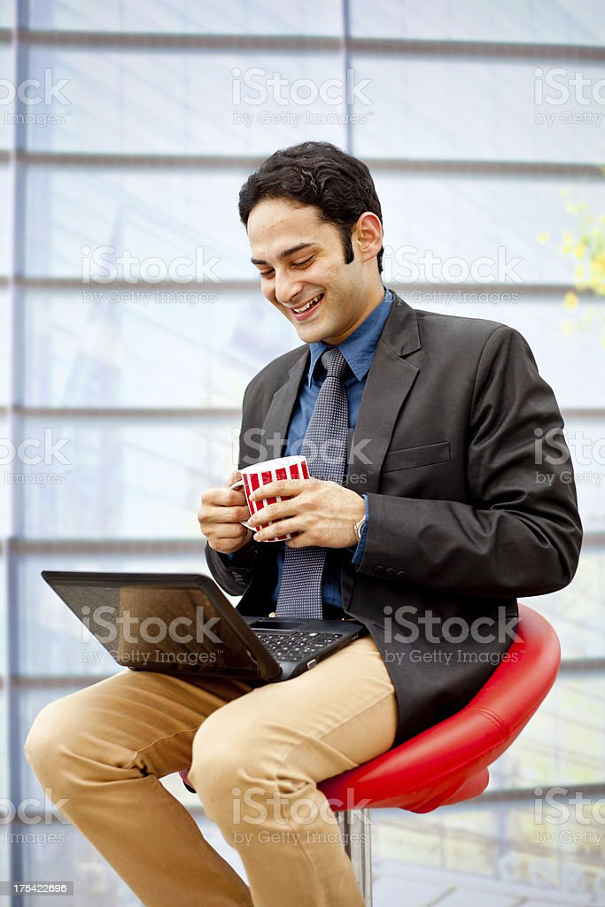 Smart Indian Businessman Standing Using Laptop and Sipping Coffee Outdoors royalty-free stock photo