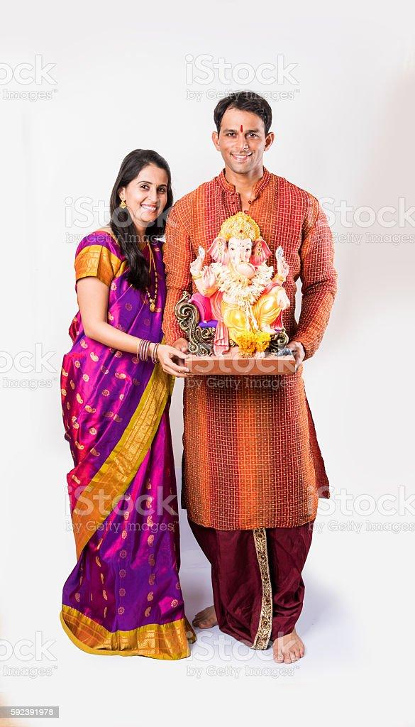 smart indian young couple holding ganesh idol or ganesha idol stock photo