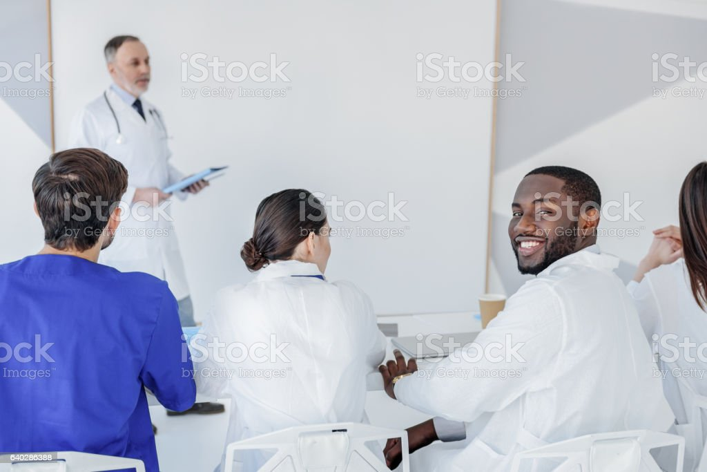 Smart interns listening to lecturer with interest stock photo