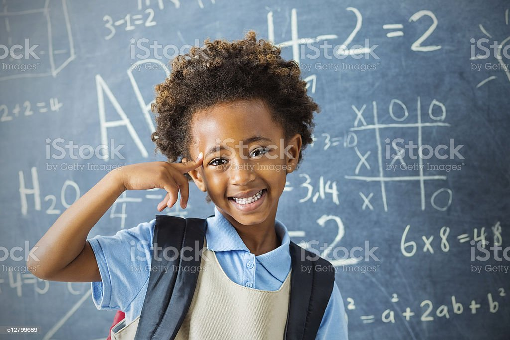 Smart kindergarten private school student pointing at head confidently stock photo