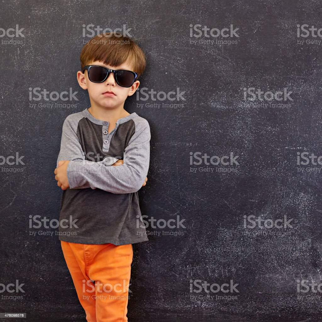 Smart little boy standing against blackboard stock photo