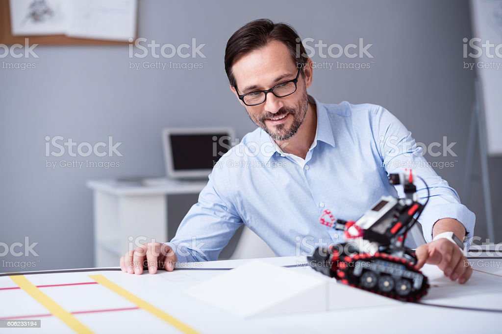 Smart man in glasses testing a little robot stock photo