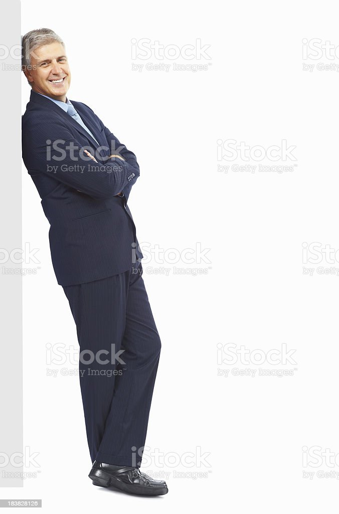 Smart, mature business man leaning against wall royalty-free stock photo