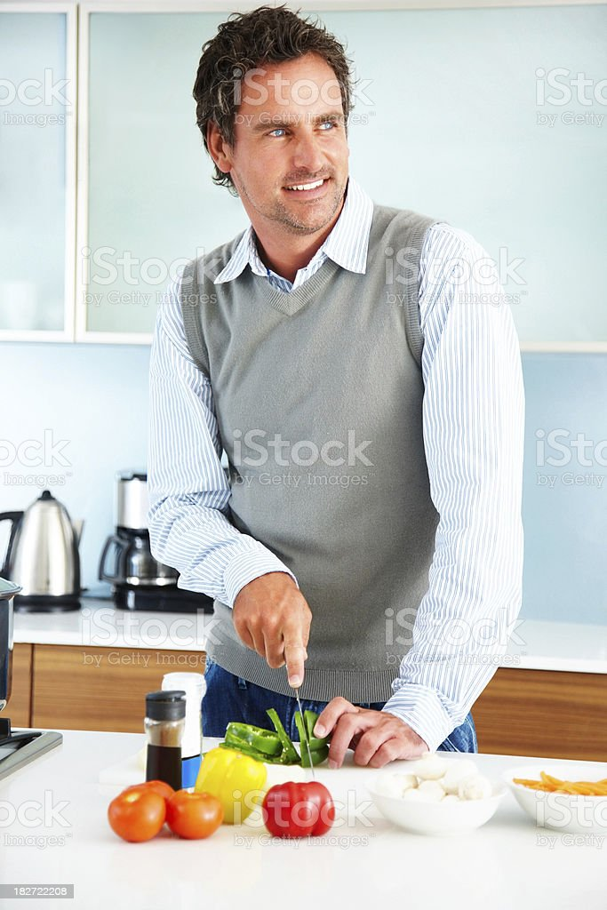 Smart mid adult man cutting vegetables in kitchen royalty-free stock photo