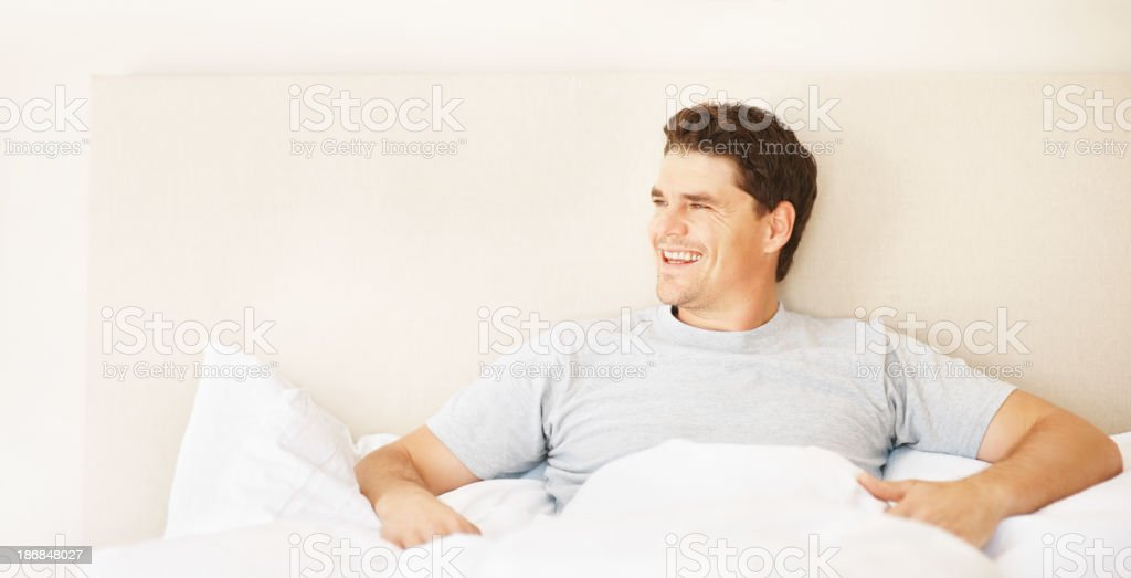 Smart mid adult man sitting in bed smiling royalty-free stock photo