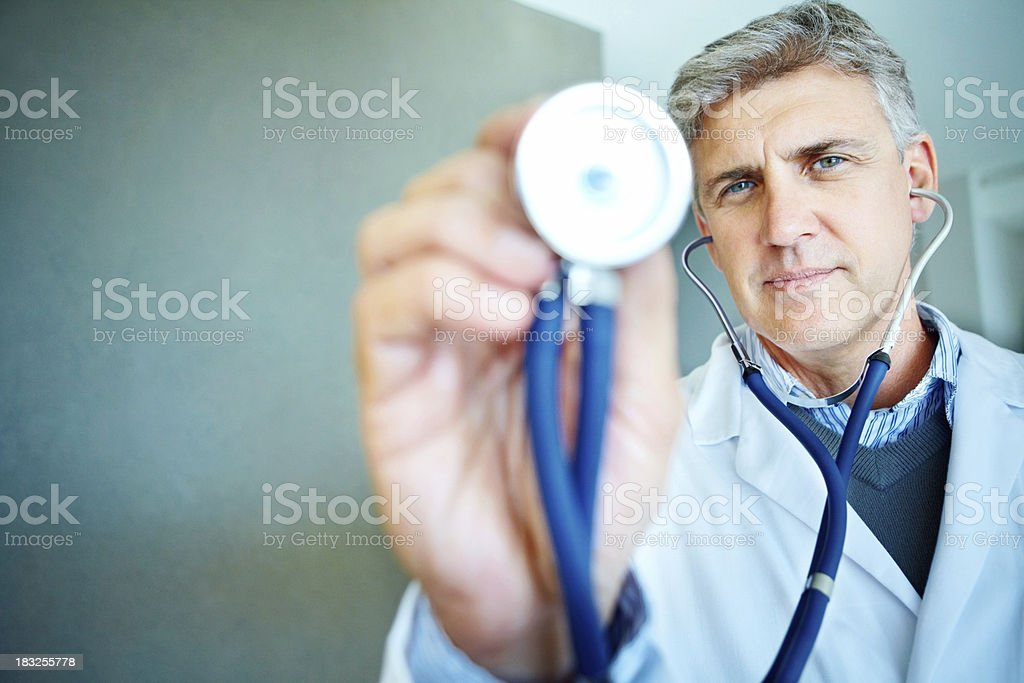 Smart middle aged doctor holding out a stethoscope royalty-free stock photo