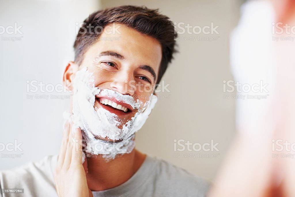Smart middle aged man applying shaving cream stock photo