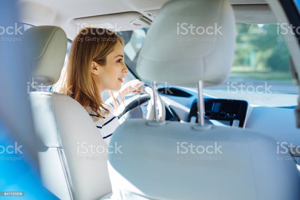 Smart nice woman sitting in the car stock photo