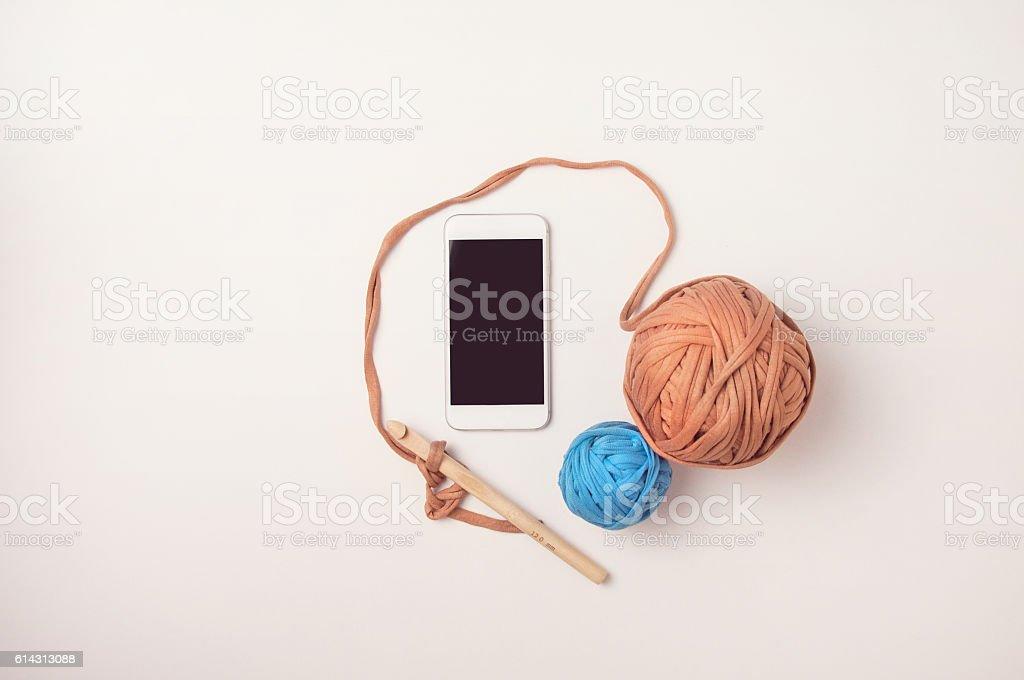 Smart phone and balls of T shirt yarn stock photo