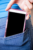 Smart phone close-up in woman's back pocket. Blank screen copyspace.