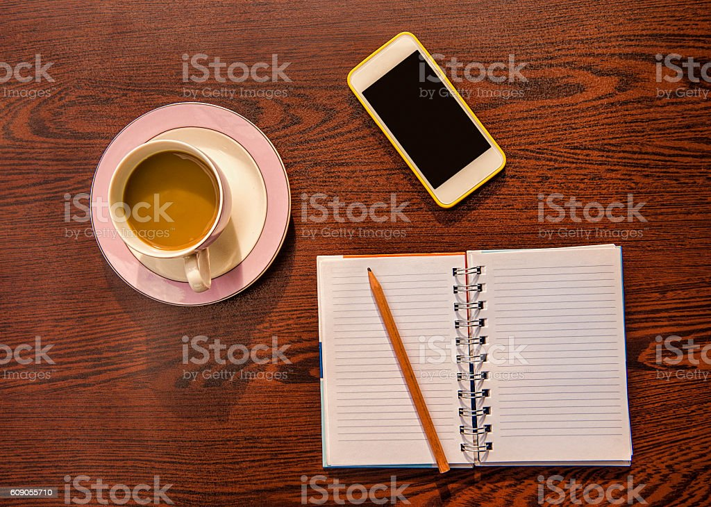 Smart phone, coffee and note pad on wooden table stock photo